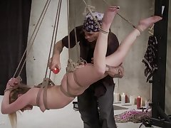 He plays with her body while she is hanging from the ceiling